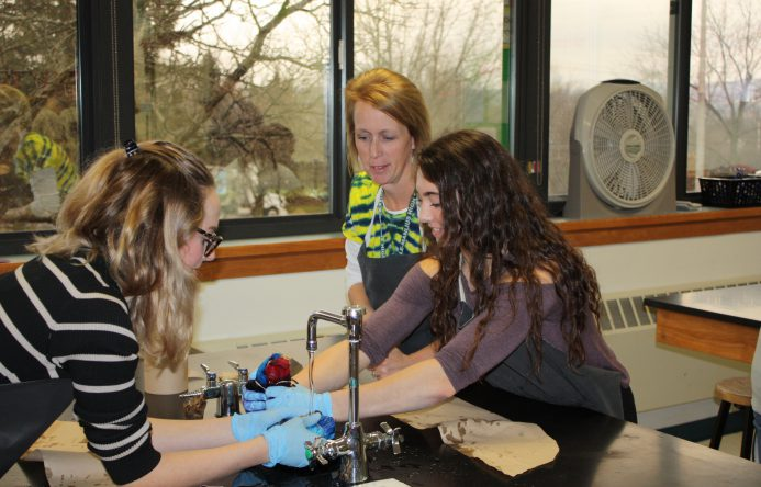 Two female students wash t-shirts in science sink while their teacher watches.