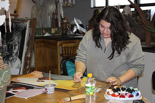 Student painting in art studio.