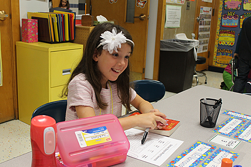 Student seated at classroom table smiling.