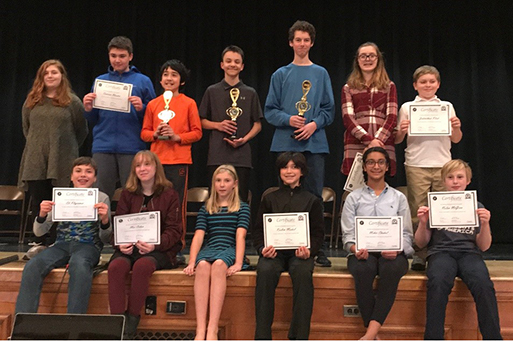 group photo of geography Bee participants holding certificates and trophies.