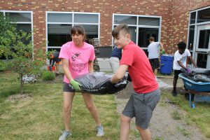 This is an image of a student and staff member carrying a bag of mulch.