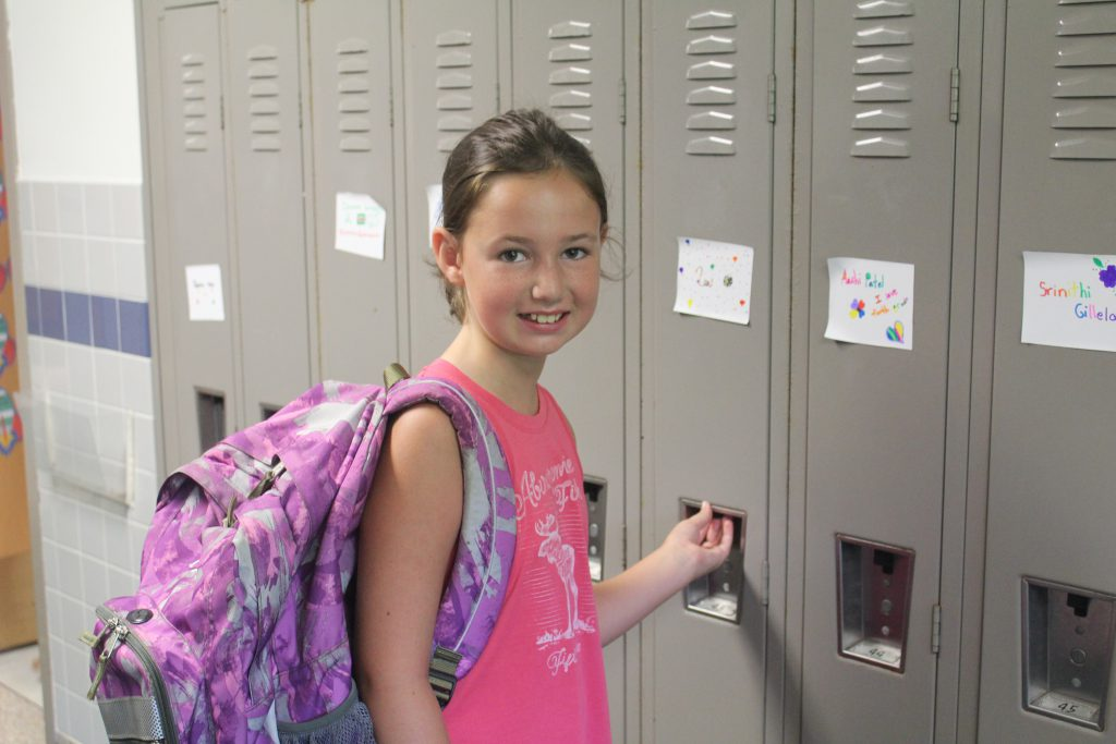 This is an image of a female student opening a locker