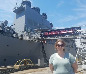 This is an image of Melissa Asztalos standing in front of the USS Ramage.