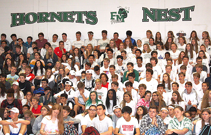 This is an image of many students sitting on the bleachers in the high school gymnasium