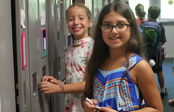 This is an image of two female students standing by a locker