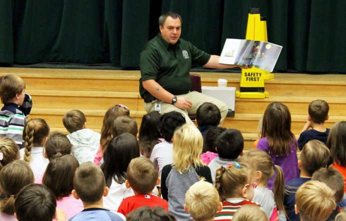 This is an image of Office Paul reading a story to a group of elementary students