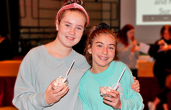 This is an image of two girls smiling and holding ice cream