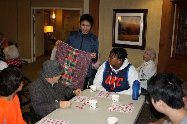 A male student holds up a quilt so a resident can see it better.