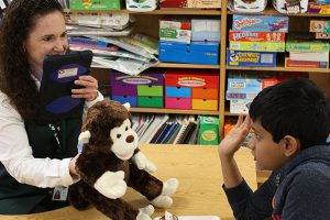 This is an image of a student working with a teacher and a Bluebees pal.