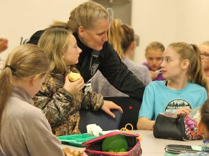 This is an image of Officer Beth Brainard chatting with students during lunch
