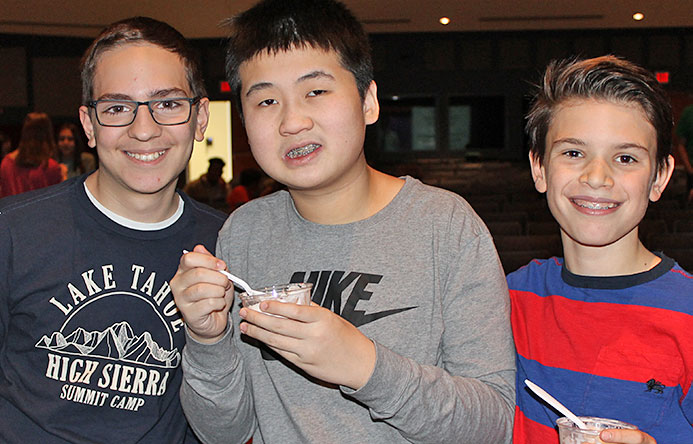 This is an image of three male students eating ice cream