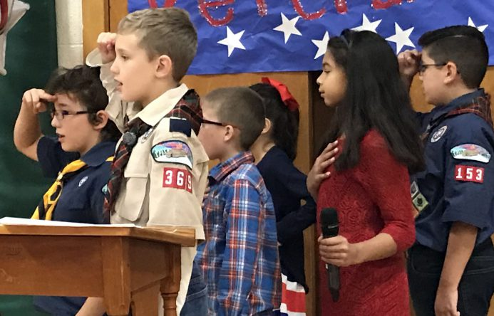 This is an image of elementary school students saluting the flag