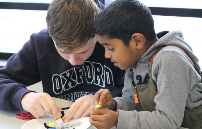 This is an image of two students working closely on a project