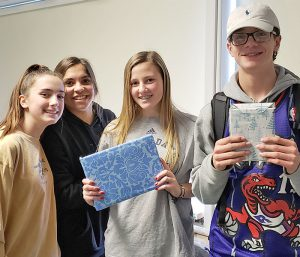 This is an image of four F-M students holding gifts and smiling