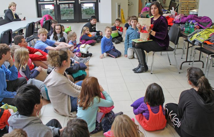 This is an image of Mrs. Brenner reading a book to students