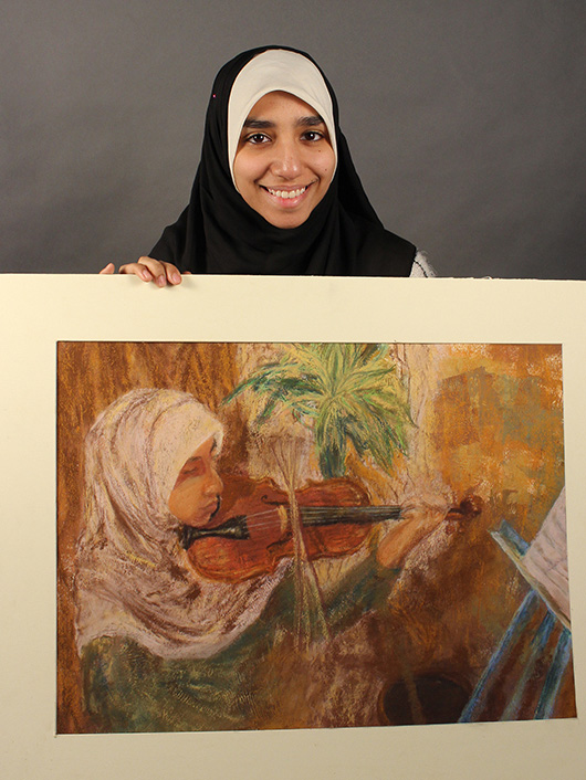This is an image of an F-M student holding her artwork