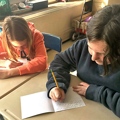 This is an image of two students writing cards