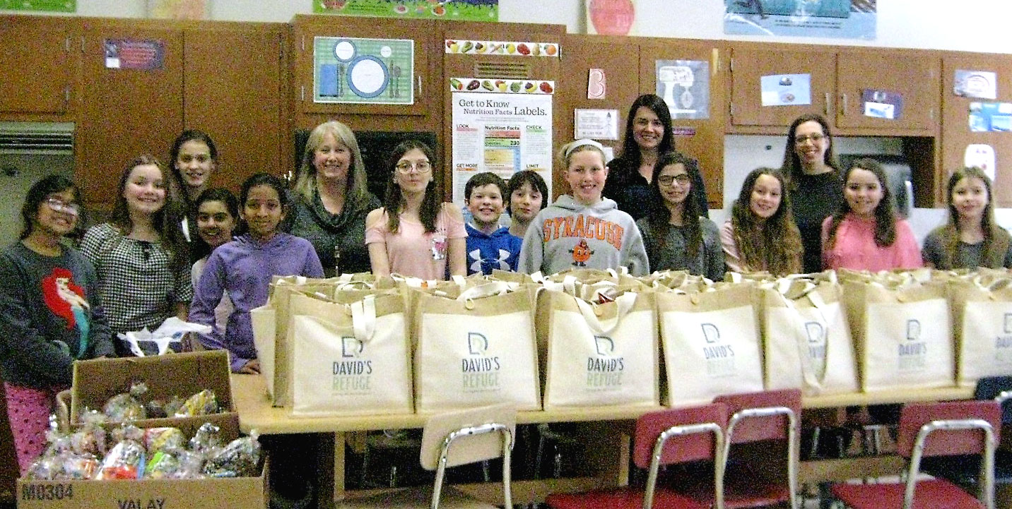 This is an image of students standing with hospitality bags that they prepared for David's Refuge