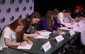 Students seated at a long table sign paperwork.