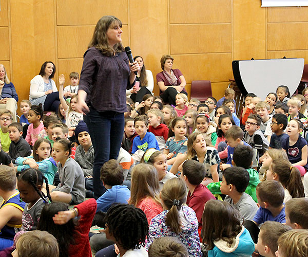 This is an image of Kate Messner talking to elementary school students