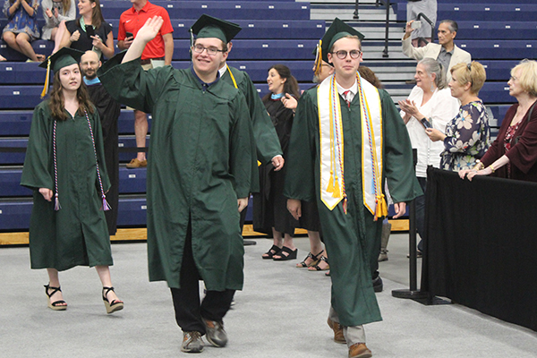 This is an image of two students walking during graduation