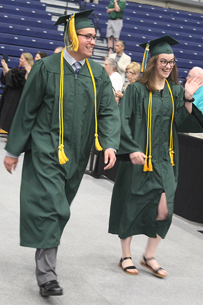 This is an image of two students walking at graduation