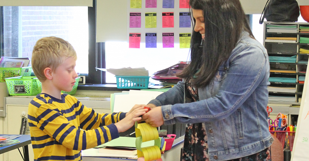This is an image of a teacher helping a student make a paper chain