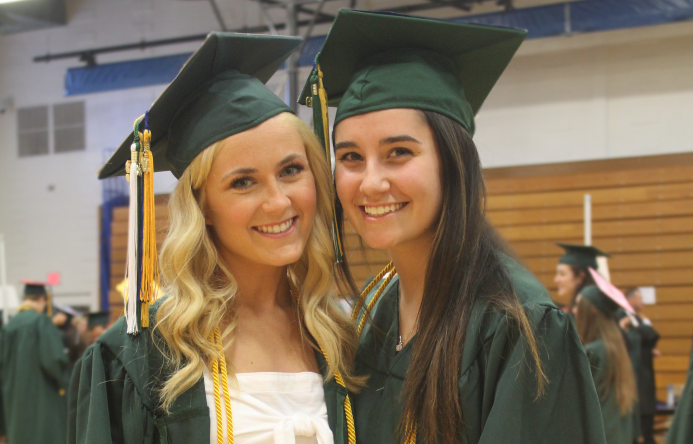 This is an image of two students smiling at graduation