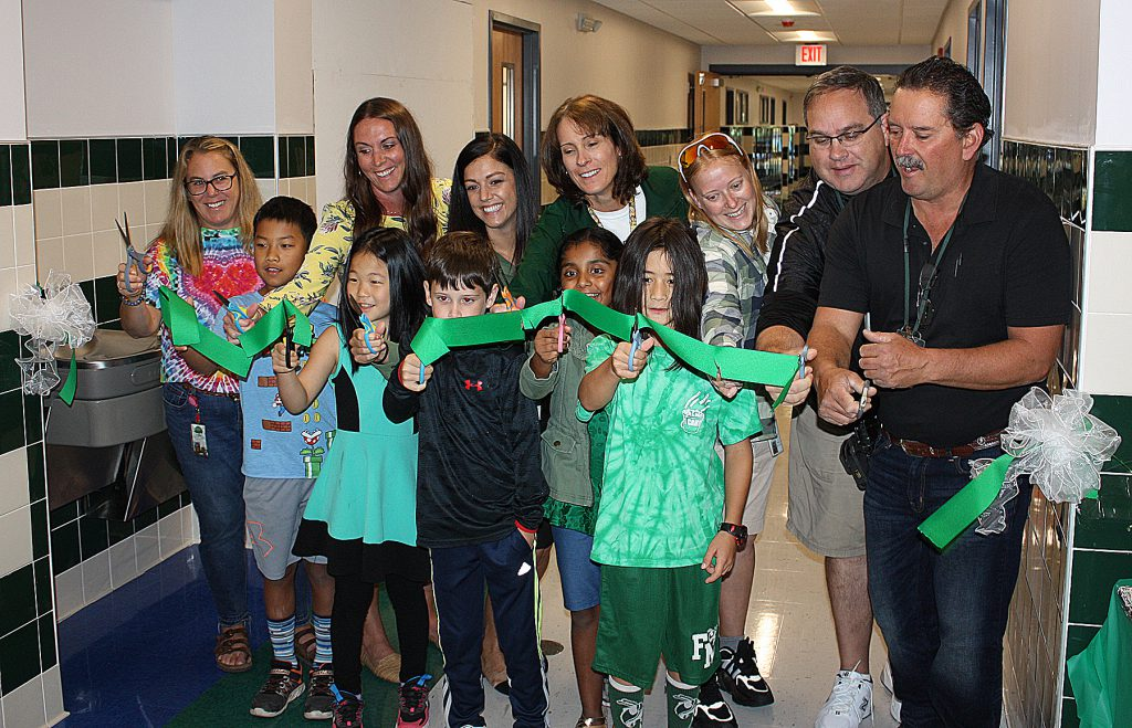 Group of people using scissors to cut a green ribbon stretched across a hallway.
