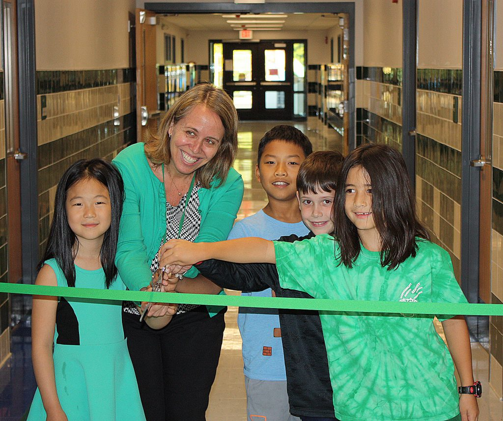 This is an image of four students and a school principal cutting a ribbon