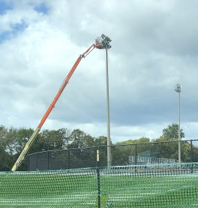 A boom lift stretches to the top of a stadium light post.