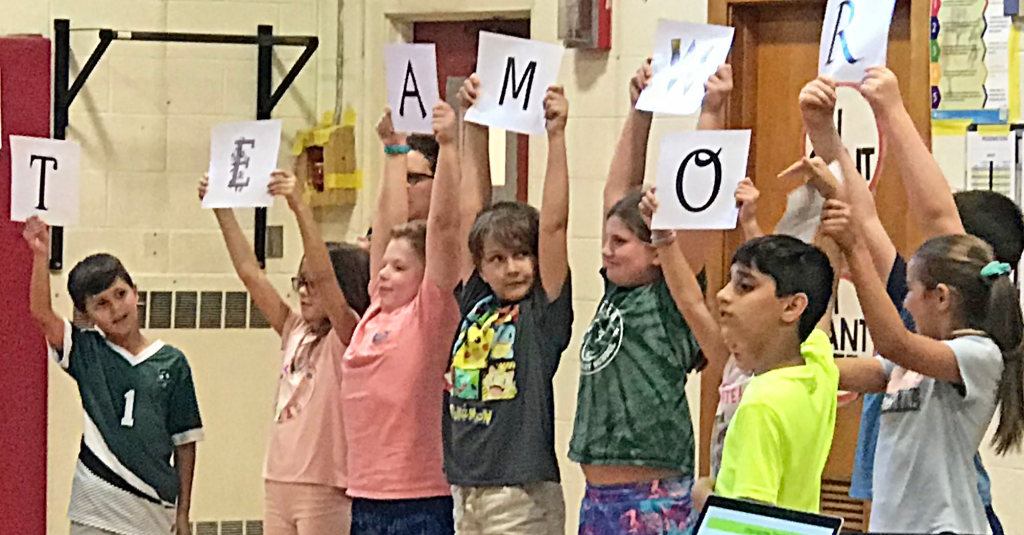 This is an image of students holding up a teamwork sign