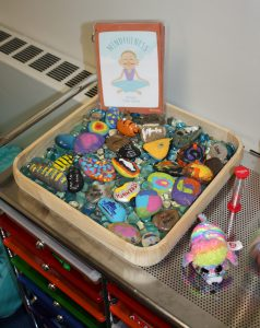 Painted rocks in a tray make a rock garden.