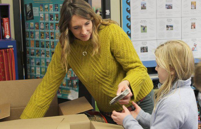 Teacher handing coffee sleeves to student.