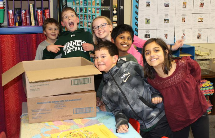 Group of students standing by a cardboard box.