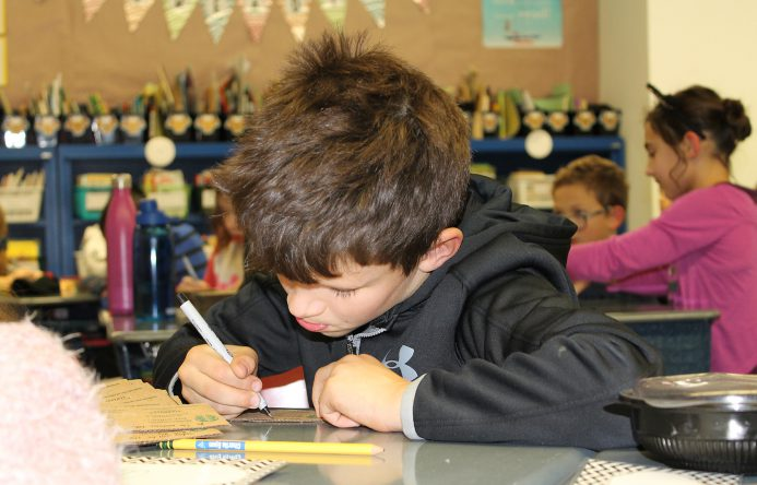 Boy seated at desk writing.