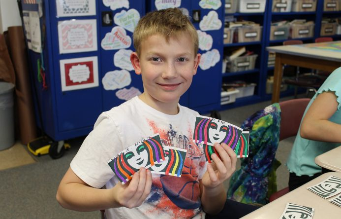 Boy holding up colored coffee sleeves.