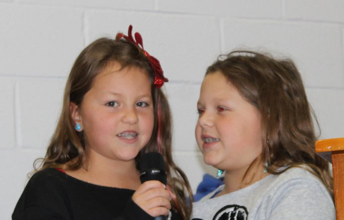 Two girls, both holding and talking into a microphone.