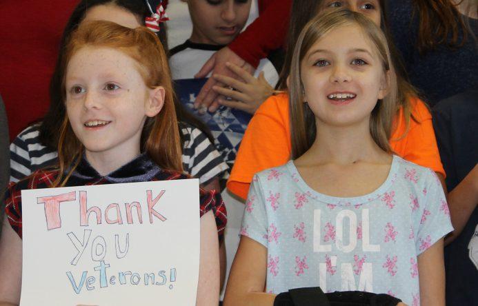 "Girl holding ""Thank you Veterands"" sign, left, girl smiling, standing, right"