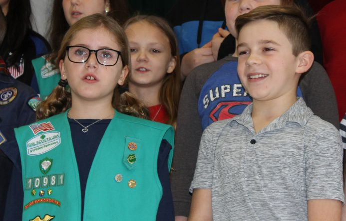 Girl. left and boy, right, standing while singing.