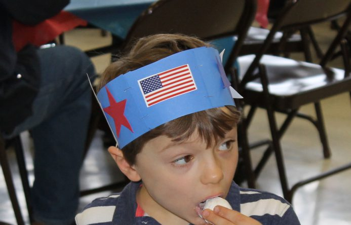 Boy waering paper red, white and blue hat eating a donut hole.