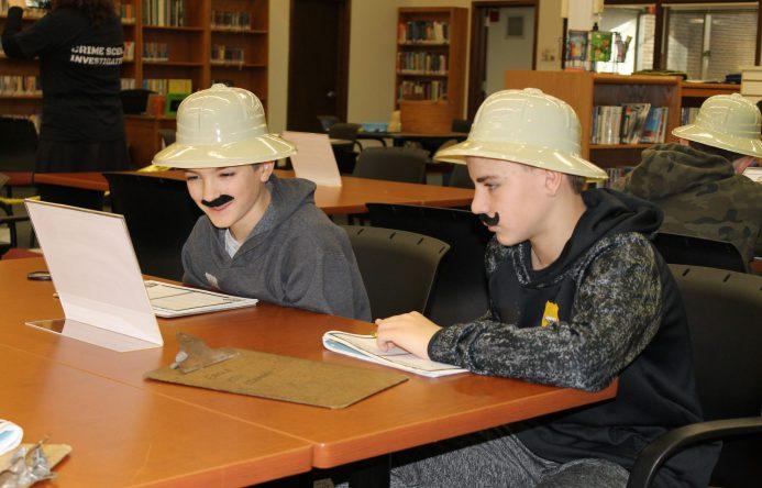 Tow boys wearing safari hats seated at table.