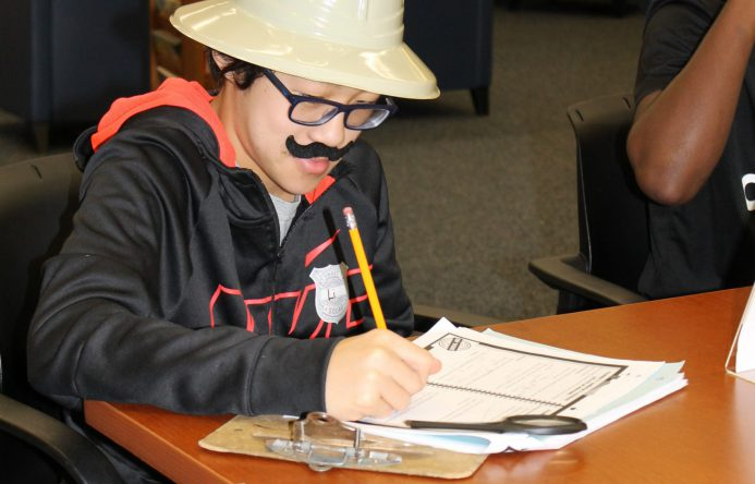 student seated at table, wearing safari hat and fake mustache, taking notes.