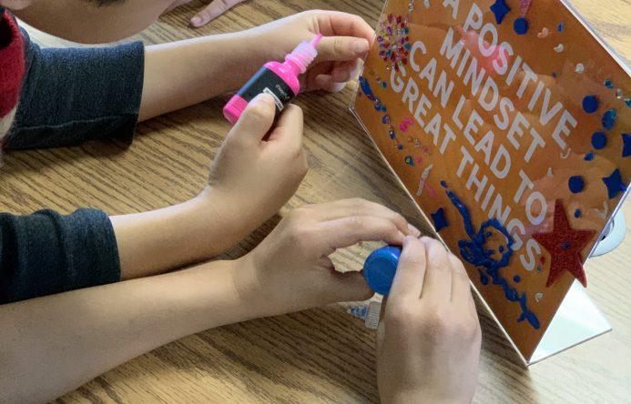 children's hands decorating frame.
