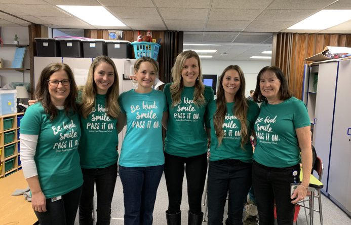 Group of women standing in a line, all wearing the same t-shirt.