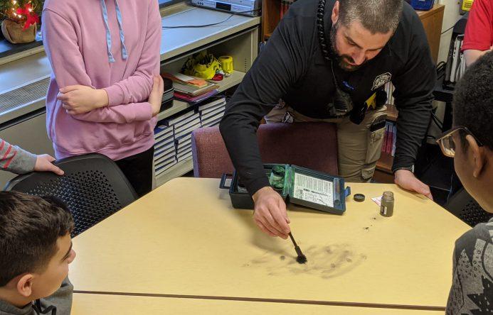 Officer Filip dusting table for fingerprints.