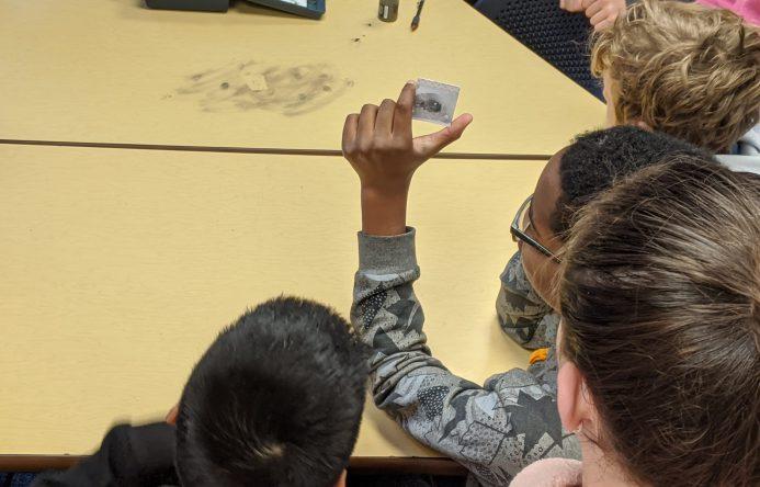 Student holding up fingerprint slide.