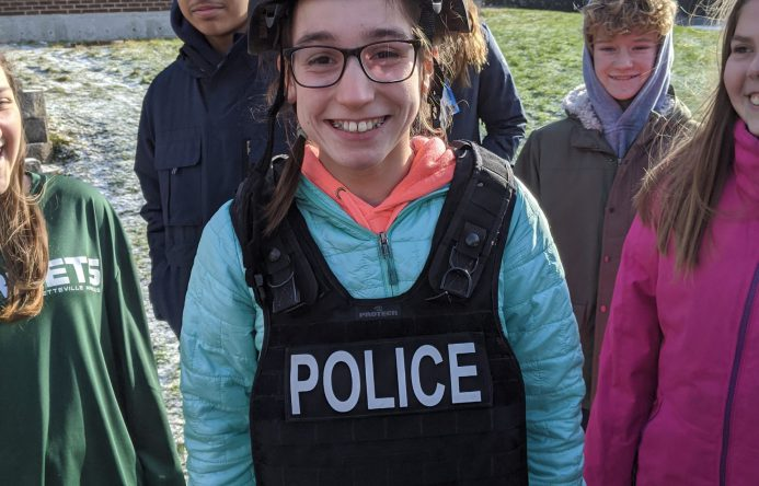 Student wearing police helmet and vest.