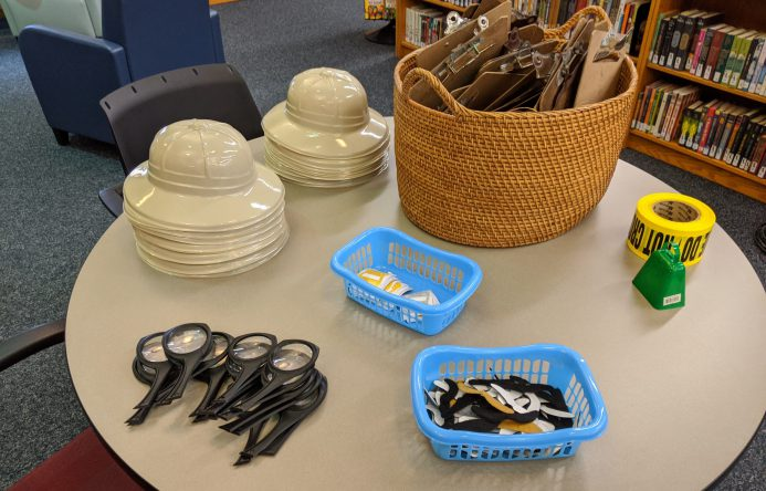 Safari hats, magnifying glasses and other accessories laid out on table.