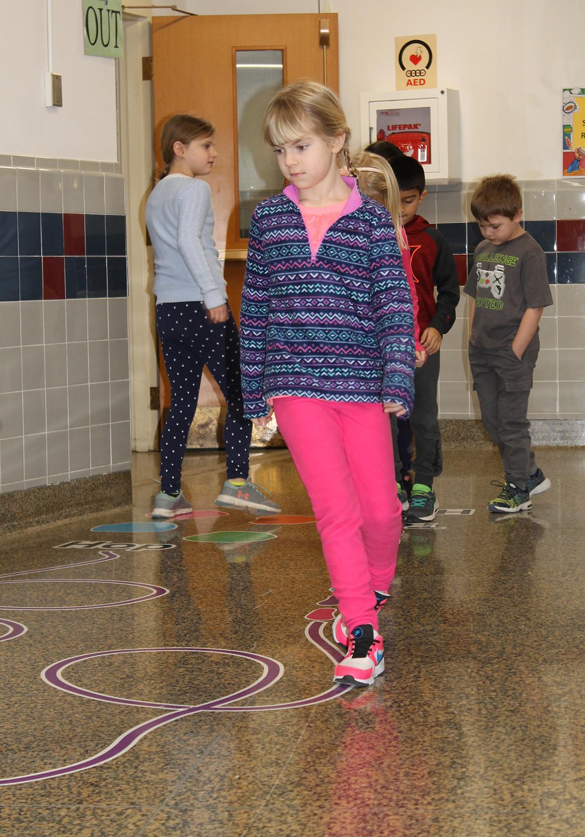 Students walking on sticker path in hallway.